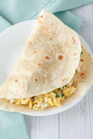 breakfast egg burrito with cheese,  herbs and spices on white plate Imagens