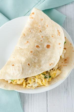 huevos revueltos: desayuno burrito de huevo con queso, hierbas y especias en la placa blanca