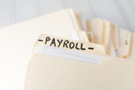 geel papier map gelabeld PAYROLL met informatie over medewerkers van een klein zakelijke onderneming