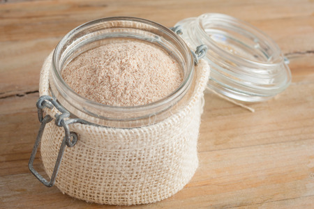 psyllium husks powder in glass jar over wooden rustic background Standard-Bild