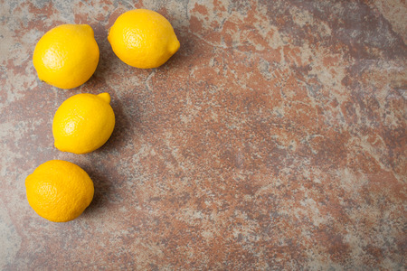 room for text: four whole lemons on textured background, overhead shot with room for text