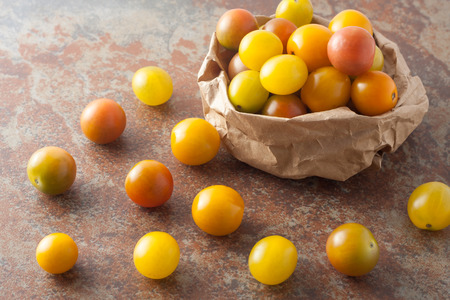 a bag of fresh picked ripe organic colorful mini tomatoes on textured stone background, top view Imagens