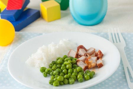 l plate: baby food: finely chopped tender cutlet and green peas on white plate