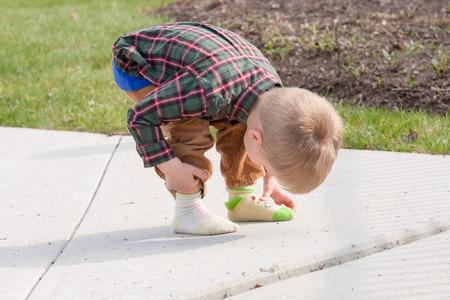 confundido: niño confundido vestido con dos calcetines diferentes mirar y tocar sus pies fuera en una acera