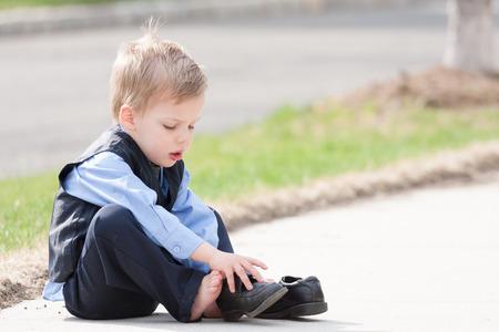 schattige peuter jongen in pak proberen om zijn schoenen aan te trekken Stockfoto