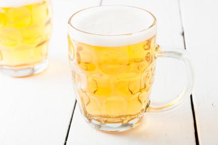 un bottled: light beer in glass mug on white wooden table