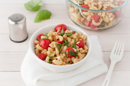 Italian macaroni salad with tomatoes and fresh basil in white bowl over white background