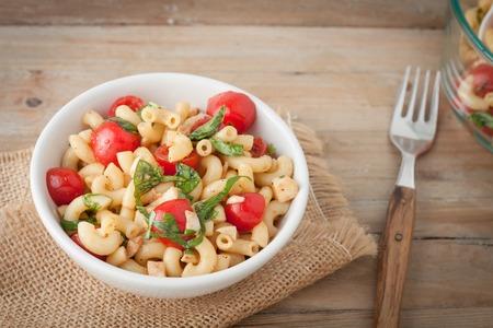 Italiaanse macaroni salade met tomaten en verse basilicum in witte kom over houten achtergrond