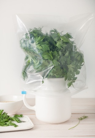 stored: close up of properly stored fresh herbs - in water and wrapped in plastic bag