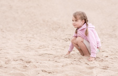 pig tails: little girl with pig tails kneeling on the sand and looking ahead
