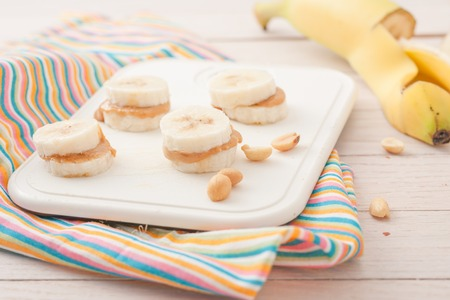 banana slice: banana slices with peanut butter on white chopping board