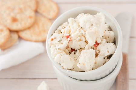 chunks: chunks of cheese with sundried tomatoes, herbs and spices in white bowl Stock Photo