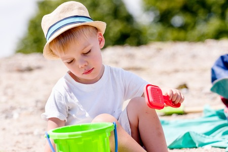 sifter: toddler boy wearing a hat and a white shirt playing with sand sifter on a beach Stock Photo