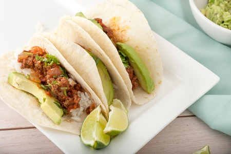 three homemade soft tacos with ground meat, avocados, cilantro and rice isolated on white background, room for text Imagens