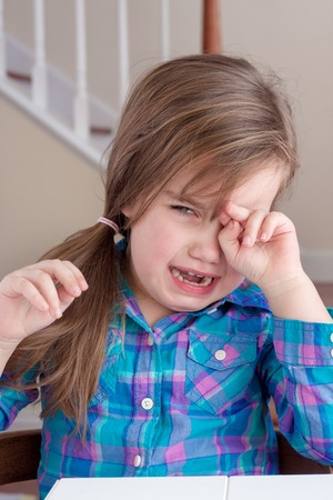 adorable girl in blue shirt crying and wiping her eye Standard-Bild