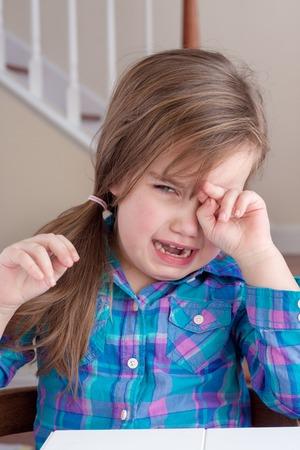 schattig meisje in het blauw shirt huilen en veegde haar ogen