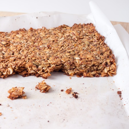coconut oil: fresh home made granola bars made with coconut oil, nuts and seeds  on a baking sheet, isolated Archivio Fotografico