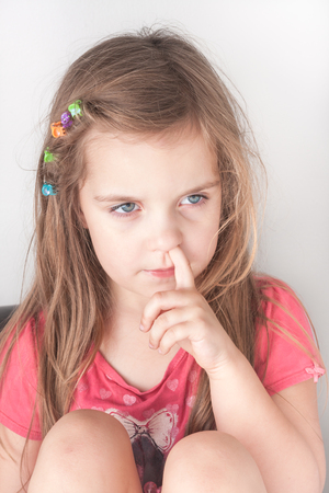 nose picking: a portrait of a little girl picking her nose, isolated Stock Photo