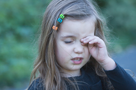 feel affection: portrait of tired or bored little girl wiping her eye Stock Photo