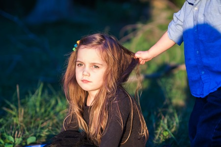 outdoor portrait of a beautiful little girl while her toddler brother is pulling her hair