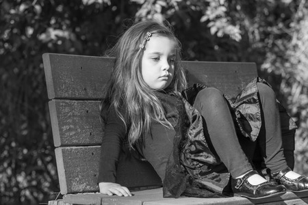 feel affection: tired or bored little girl sitting on a bench in a park, black and white image