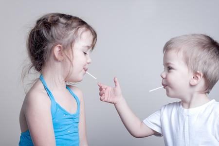 broers en zussen die pret met lolly's - kleine broertje probeert lollypop van zijn zus te grijpen, horizontale beeld