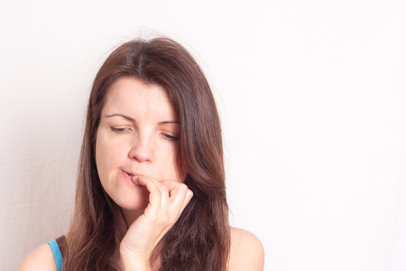 a portrait of a young woman biting her nails, horizontal image Banque d'images