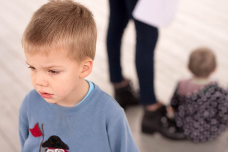 sad blond boy jealous about being neglected by his mother or caregiver who is giving attention to another child