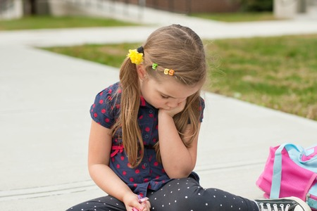 harass: caucasian sad little girl sitting on a sidewalk in front of school and worrying or crying Stock Photo