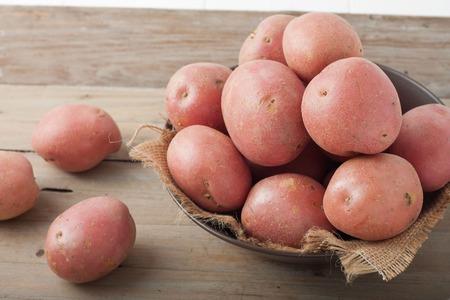 batata: grandes papas rojas en un plato sobre fondo de madera