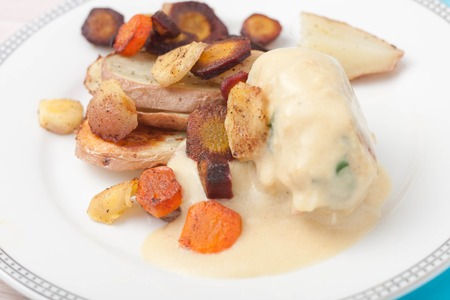 parsnips: a white bowl of roasted root vegetables: carrots, parsnips, sliced and roasted with honey and cinamon served with chicken meatballs stuffed with cheese, ham and parsley in white wine sauce