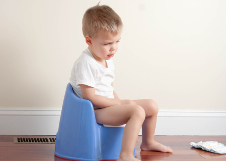 sad toddler boy wearing a white t-shirt sitting on a blue potty Stock Photo
