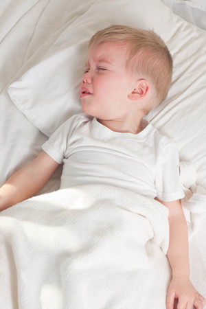 a sick blond toddler wearing white t-shirt lying in bed and crying Banque d'images
