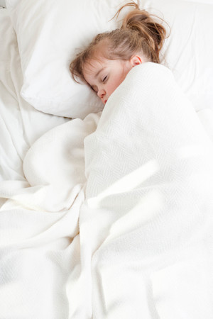 pony tail: a little girl with pony tail sleeping covered with white blanket