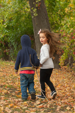hispanic girl: two young children walking in a park dragging together a long stick on a fall day