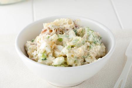 mayonesa: Cerca de ensalada de patatas casera hecha con papas rojas, apio, cebollas rojas y hierbas frescas en un recipiente blanco