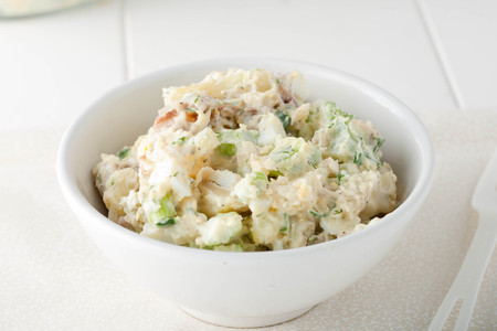 close up of homemade potato salad made with red potatoes, celery sticks, red onions and fresh herbs in white bowl Standard-Bild