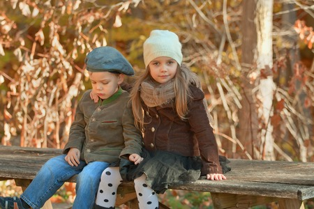 brotherly love: Brother and sister dressed up warm in hats sitting on a bench in a park on a cool autumn day