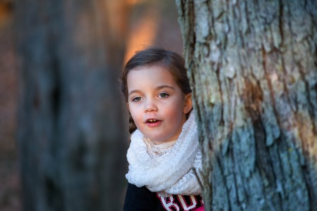 seek: a little girl waring a pink scarf is playing hide and seek in the woods hiding behind a tree late afternoon