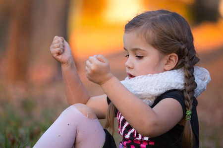 a little girl is trying to fix a hole in her tights Standard-Bild