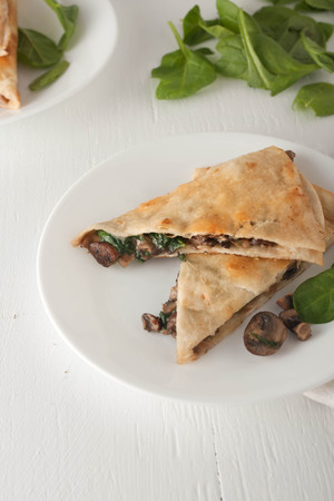 mushroom spinach quesadilla on white plate, selective focus