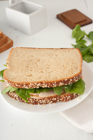sandwich with mayonaisse, turkey, cheese and fresh spinach on white plate Standard-Bild