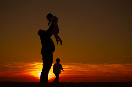 Silhouette of a single father on vacation with his two kids, picking up his daughter