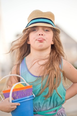 beautiful little girl carrying beach toys and wearing a straw hat showing her tongue to he mother while going to the beach, parenting concept image Stock Photo