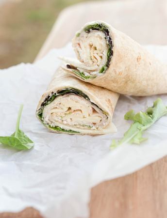 tortilla wrap: a healthy wrap with turkey, greens and cheese made with whole grain tortilla wrap on white wrapping paper, selective focus