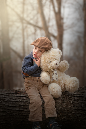 outdoor portrait of a little boy with a hat sitting on a tree and hugging a teddy bear