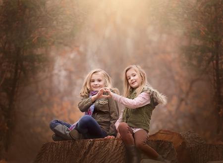 artistieke moody outdoor portret van twee blonde meisjes zitten op een log van de boom in een bos, grote artistieke expressie van vriendschap