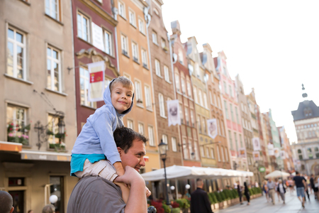role models: happy little boy on top of his fathers shoulders siteseeing european city center