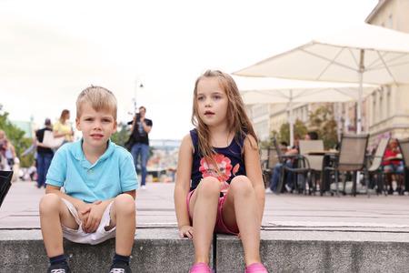 niño y niña sentada en un paso en un centro de la ciudad y hablando