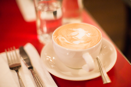 a cup of italian coffee with milk foam such as latte or cappuccino on red tablecloth